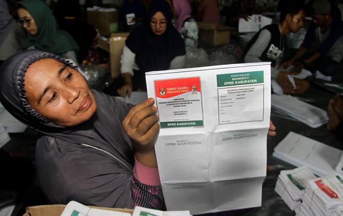 Pekerja pelipat suara menunjukkan surat suara DPRD Kabupaten Mojokerto di gudang logistik KPU di GOR Dispendik, Desa/Kecamatan Sooko.