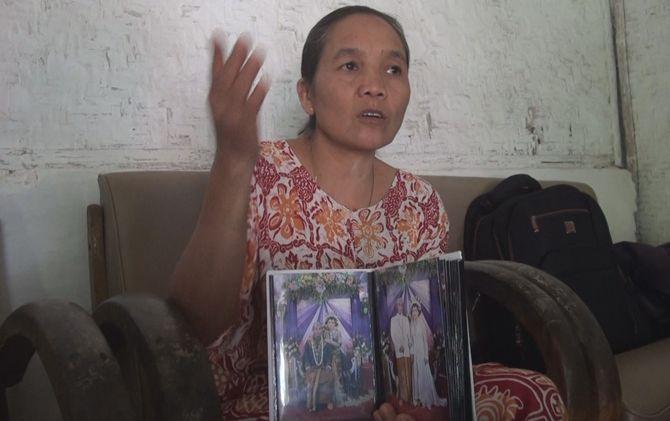 Ninik Suwarni menunjukkan foto resepsi pernikahan Khurotul Aini dan Risky.