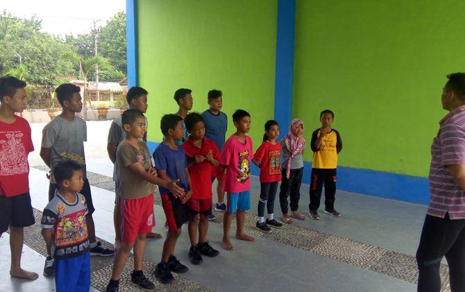 Para pegulat pemula dan junior Kabupaten Mojokerto mendengarkan arahan pelatih saat latihan rutin di SMPN 2 Trowulan.