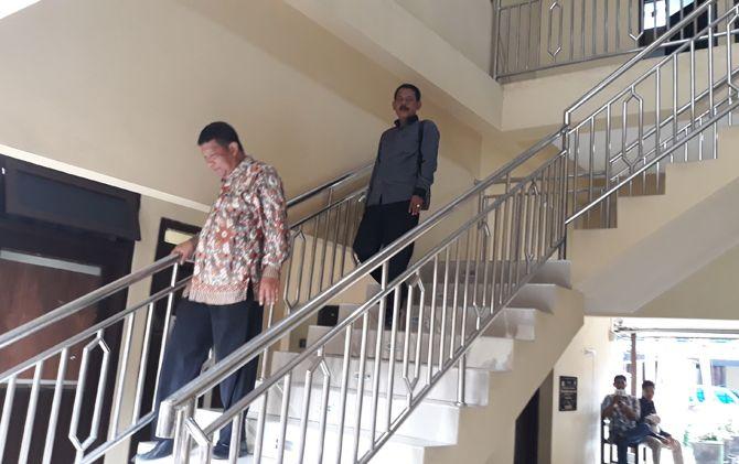 Didik Pancaning Argo dan Budiono menuruni tangga seusai diperiksa KPK di aula Mapolresta Mojokerto.