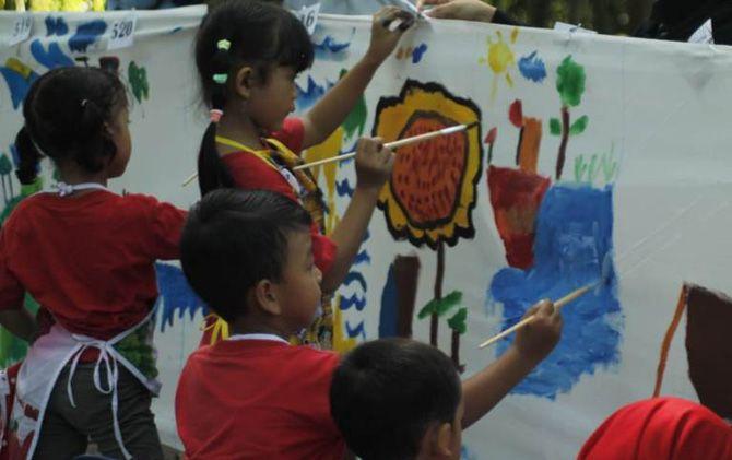 Para siswa menuangkan kanvas pada kain saat mengikuti lomba mewarnai di hutan kota Kelurahan Pulorejo, Kecmatan Prajurit Kulon yang digelar Dinas Perpustakaan dan Arsip Kota Mojokerto, Jumat (22/3).