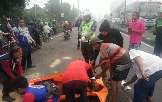 Petugas kepolisian dibantun tim relawan mengevakuasi jasad korban di Jalan Raya Bypass Desa Jatipasar, Kec. Trowulan, Kab. Mojokerto.