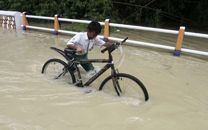 Siswa MI menerjang genangan banjir.
