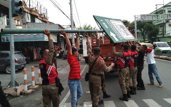 Anggota Satpol PP Kota Mojokerto menurunkan reklame diduga melanggar di Jalan Gajah Mada Jumat (5/4).