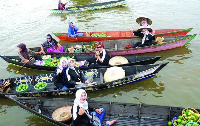 Warga dan wisatawan bertransaksi di sungai terapung Lokba Intan.