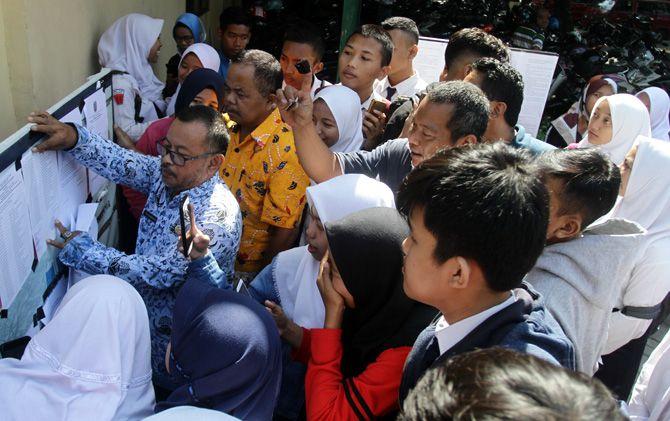 : Pengumuman PPDB jalur offline di SMAN 1 Sooko, Kabupaten Mojokerto. Calon siswa ramai-ramai mencari namanya di papan pengumuman.