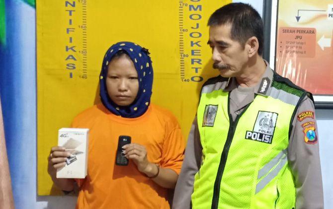 Tersangka Novi Ekasari menunjukkan handphone yang dicuri dari rumah korban di Mapolsek Sooko, Mojokerto.