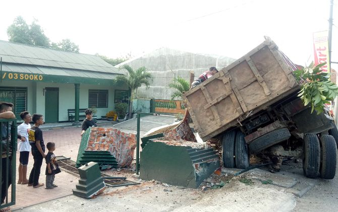 Kernet truk yang menyasar Kantor Koramil Sooko menurunkan material uruk di Jalan Raya Bypass Desa Gemekan, Kecamatan Sooko, Kabupaten Mojokerto.