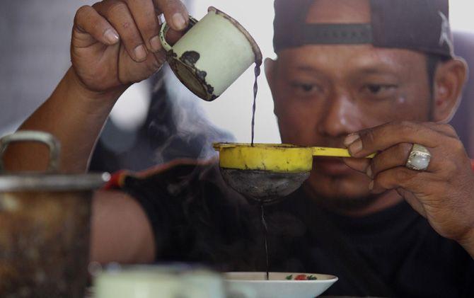 Pedagang menyaring kopi grosok sebelum disajikan kepada pelanggan di Trawas, Mojokerto.