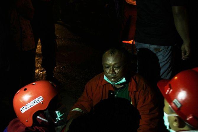 Petugas PMK mendapat pertolongan akibat mengalami sesak napas saat melakukan pemadaman gudang rongsokan di Desa Perning, Kec. Jetis, Senin (17/9).
