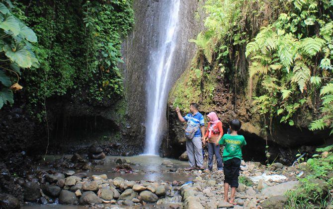 Wisatawan dalam satu keluarga menikmati pesona Air Terjun Coban Cebol.