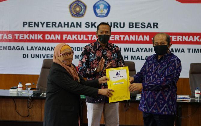 Prof. Dr. Ir. Elfi Anis Saati, M.P. (jas hitam) menerima SK Guru Besar dari Kepala LLDikti Wilayah VII Prof. Dr. Ir. Suprapto, DEA (batik ungu).