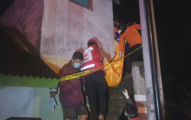 Petugas kepolisian dibantu petugas PMI Kabupaten Mojokerto mengevakuasi jasad korban, Sabtu (21/11) malam.