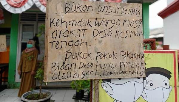 TERTUTUP: Sebuah papan ancaman terpasang di depan Polindes Desa Kesimantengah, Kecamatan Pacet.