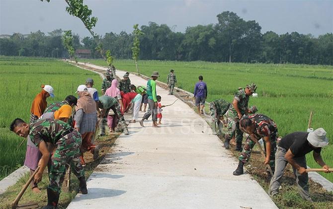 TNI dan warga gotong royong mengecor jalan desa, Senin (23/4).