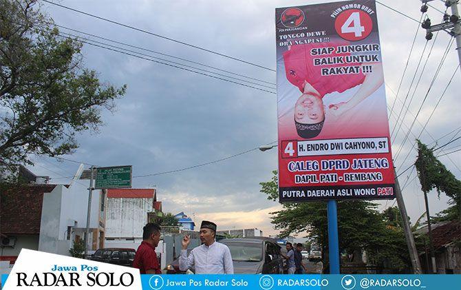 Caleg DPRD Provinsi Jateng Endro melihat pemasangan baliho terbalik miliknya di pertigaan Ada Swalayan.
