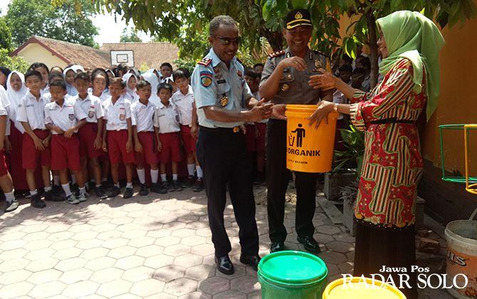 BERMANFAAT: Kalapas Sragen Yosef B. Yambise (kiri) bersama Kapolres Sragen AKBP Yimmy Kurniawan serahkan bantuan tong sampah di SDN 15 Sragen kemarin (11/12).