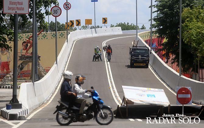 PERSIAPAN: Sejumlah petugas sedang membuat markah jalan di Overpass Manahan sebelum resmi beroperasi Jumat lusa.