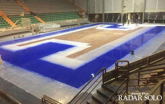 DIKEJAR WAKTU: Para pekerja tengah memperbaiki lantai di Sritex Arena yang tengah di cat ulang.