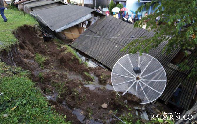 TIMPA DUA BANGUNAN: Lapangan sepak bola Desa Bulurejo, Kecamatan Bulukerto longsor karena saluran pembuangan air tak mampu menampung air hujan.