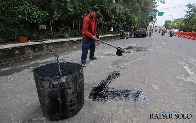 PERBAIKAN: Pekerja menambal lubang jalan di sekitar overpass Manahan kemarin (22/1).