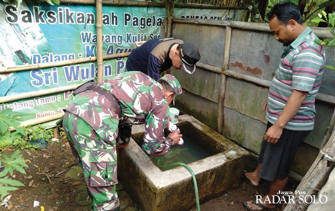 PENYISIRAN: Anggota TNI dilibatkan memantau jentik nyamuk aedes aegypti di tempat penampungan air warga.