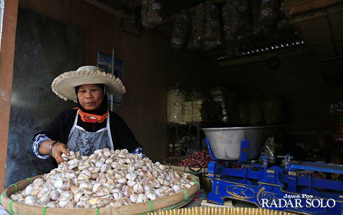 AKTOR UTAMA: Seorang pedagang bawang putih sedang merapikan dagangannya di pasar darurat Pasar Legi. Bawang putih pemicu utama inflasi April.