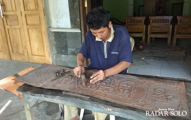 TEKUN: Seorang perajin tembaga Desa Tumang, Kecamatan Cepogo, Boyolali sedang menyelesaikan ukiran kaligrafi, kemarin. Ramadan ini pesanan kaligrafi dari tembaga membeludak.