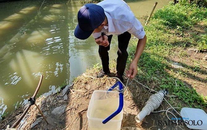 TERCEMAR: Petugas DLH saat mengecek kondisi air di salah satu aliran sungai di Karanganyar