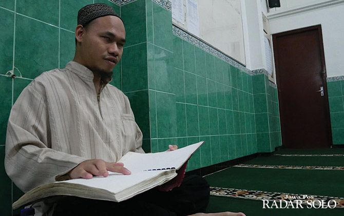 KHUSYUK: Abdul Majid mengaji dengan Alquran braille di Masjid Al Wahab.
