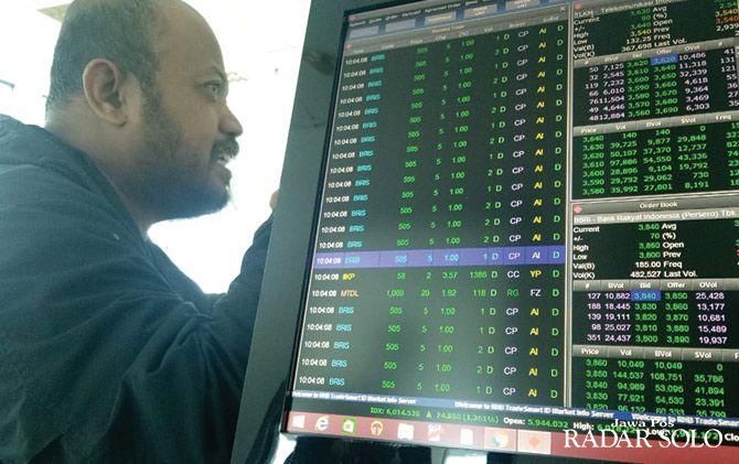 JANGKA PANJANG: Eko Rochmadi mengamati layar untuk memantau perkembangan pasar modal.