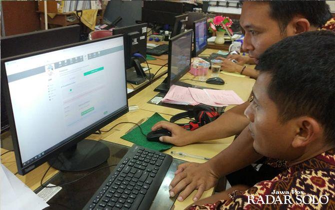 DEMI ANAK: Salah seorang orang tua siswa tengah mencoba sistem PPDB online.