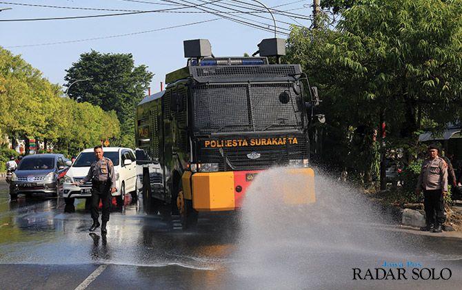 BERTEKANAN TINGGI: Kendaraan water canon milik Polresta Surakarta menyemprot kotoran kuda di sekitar Stadion Manahan kemarin (20/6).