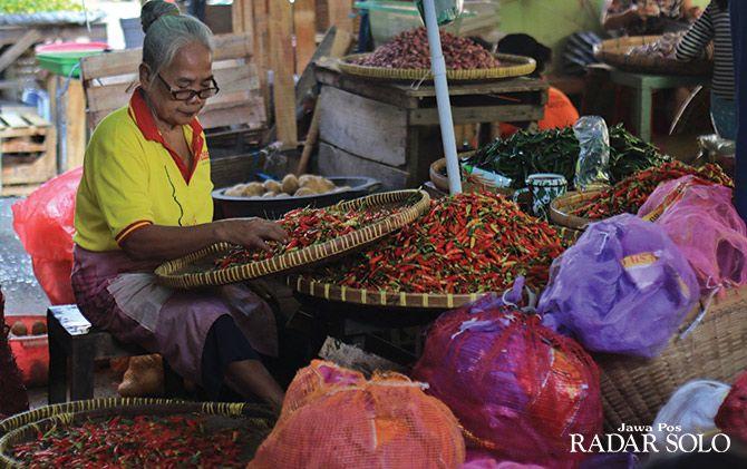 MAKIN MAHAL: Seorang pedagang cabai rawit merah memilah yang kualitasnya bagus di Pasar Legi, kemarin. Semua jenis cabai mengalami kenaikan sejak sepekan ini.