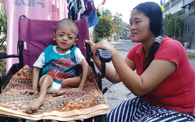 Abrizam duduk di kursi roda bersama ibundanya Anita kemarin.