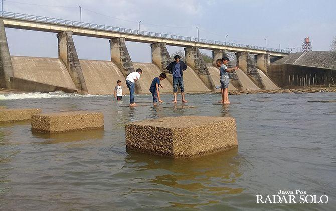 MENGERING: Sejumlah anak bermain di Dam Colo.