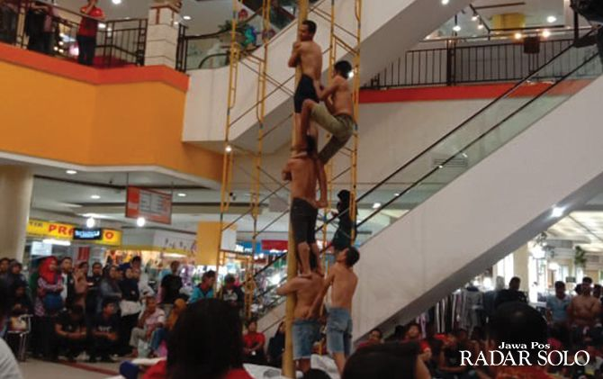 ADU KUAT: Lomba panjat pinang di Atrium Solo Grand Mall, kemarin (28/8). Lomba ini diikuti jajaran manajemen, tenant, dan mitra.