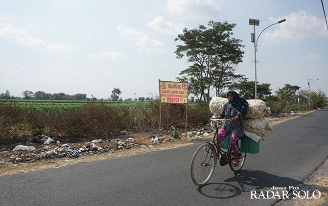 BAU MENYENGAT: Warga melintasi Jalan Pedan-Trucuk, Desa Keden, Pedan yang dipenuhi sampah.