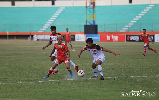 Bomber Persis Solo Hapidin dikawal dua pemain Madura FC di Stadiun Wilis Madiun