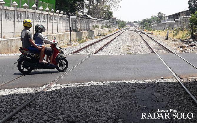 Pengendara melintas di perlintasan sebidang kereta api di Palur