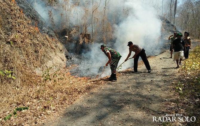 DAMPAK KEMARAU: Petugas pemadam kebakaran dibantu polisi, TNI dan relawan memadamkan api yang melanda Gunung Gandul di Wonogiri Kota, kemarin (11/10).