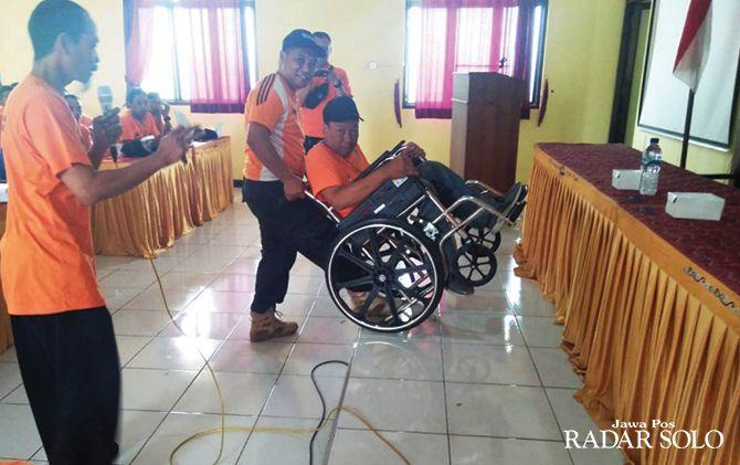 PENTING: Relawan mempraktikkan cara menolong korban bencana kaum disabilitas.