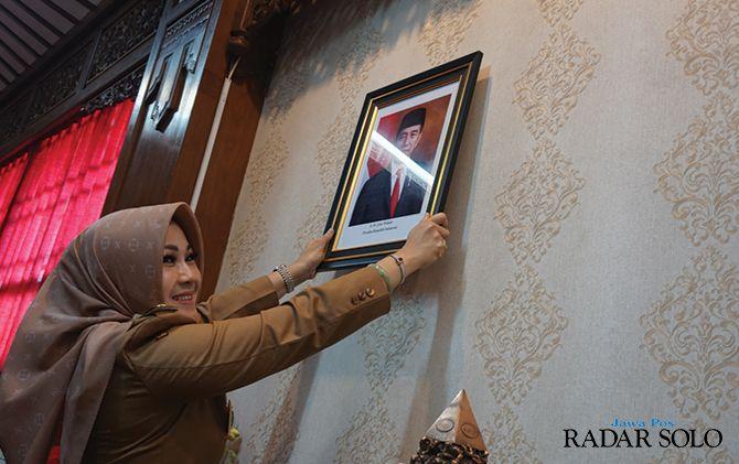 HARAPAN BESAR: Bupati Klaten Sri Mulyani saat mengganti foto presiden dan wakil presiden yang baru di ruang kerjanya, kemarin (21/10).