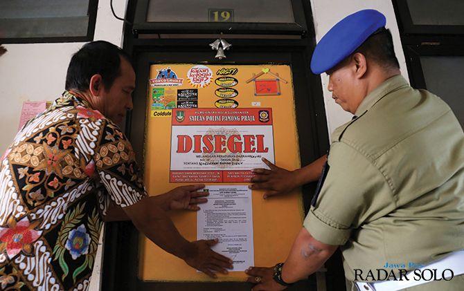 MELANGGAR: Petugas Satpol PP menempel stiker tanda segel di pintu kamar rusunawa yang menunggak biaya sewa, Rabu (30/10).
