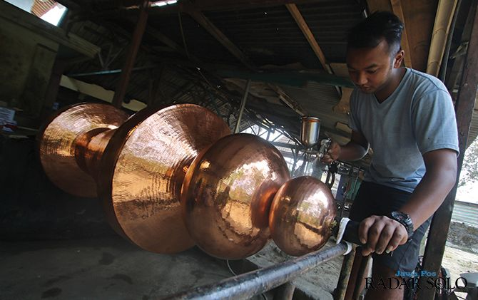 FINISHING: Perajin menyelesaikan pesanan tembaga di Dusun Tumang, Desa/Kecamatan Cepogo, Boyolali yang hendak diekspor, belum lama ini.
