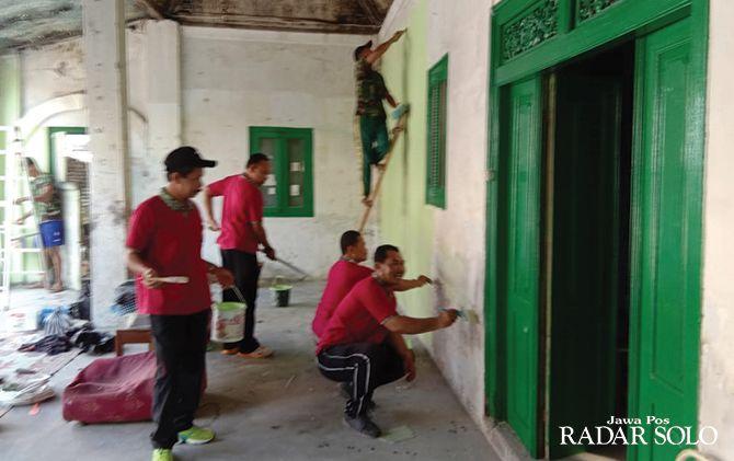 GOTONG ROYONG: Kerja bakti personel TNI-AD dan RST Slamet Riyadi di rumah Slamet Riyadi.