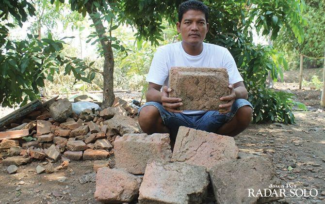 AKAN DISELIDIKI: Purnomo menunjukkan batu bata kuno yang dia temukan saat menggali tanah.