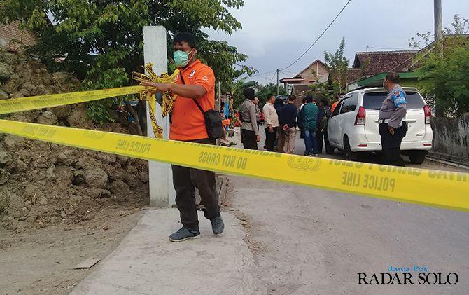 Anggota polisi memasang police line saat penggeledahan di rumah kontrakan di Desa Siwal, Polokarto