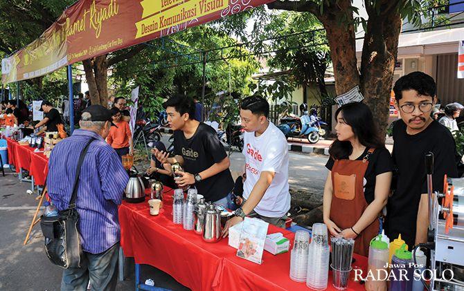 EVENT RUTIN: Peserta Soloborasi berinteraksi dengan pengunjung CFD yang menanyakan seputar pembuatan minuman kopi di depan Loji Gandrung, kemarin pagi (24/11).