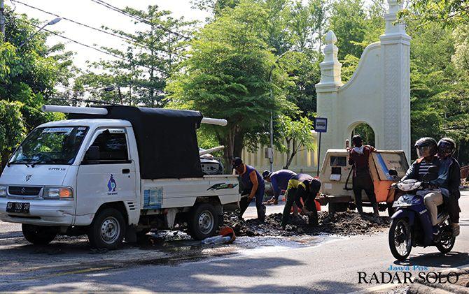 RUSAK: Petugas PDAM memperbaiki jalan rusak akibat pipa bocor di Jalan Slamet Riyadi, kemarin (26/11).